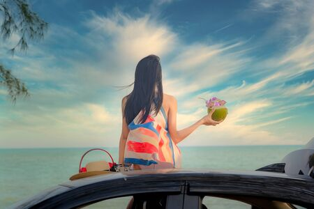 woman sitting on the car roof cheerfully with enjoy fresh coconut fruit in hand, summer and vacation on the sea beach