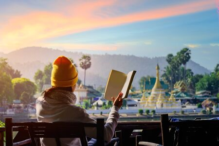 woman traveller relax sitting on the terrace reading book in the light of morning, Mae Hong son, wat Chong Kham the popular for tourist place
