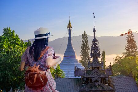 woman traveller enjoy trip visiting temple and mist foggy in light of morning, Mae Hong son province in Thailand, wat Phra That Doi Kong Mu the popular for tourist place in Northern part of Thailand