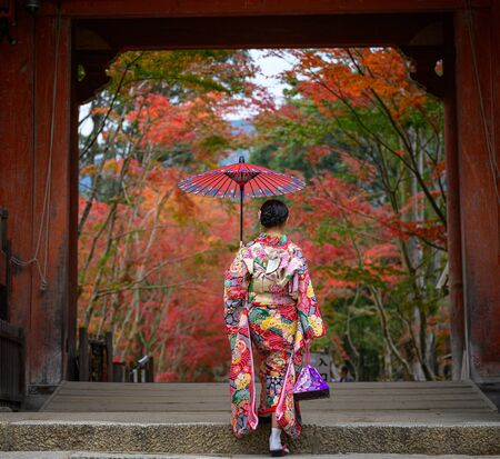 woman holding retro umbrella in old fashion style traditional kimono, swalks alone in the middle of park of the village garden in autumn, travel and visit japan on incoming sport event