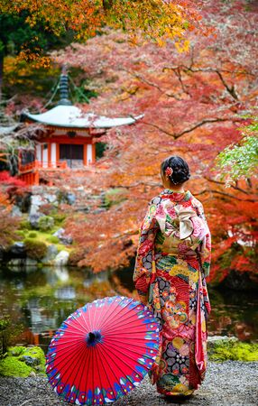 woman holding retro umbrella in old fashion style traditional kimono, stand alone in the middle of park of the village garden in autumn, travel and visit japan on incoming sport event