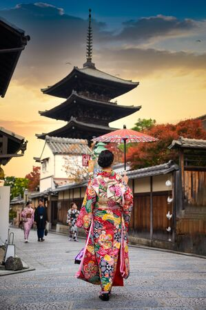 woman holding retro umbrella in old fashion style traditional kimono, walks  in the middle  park of garden village in autumn, travel and visit japan on incoming sport event