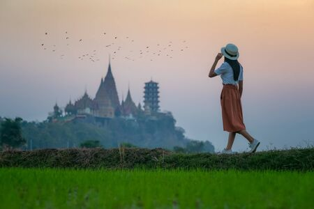 Young woman walks on the field of rice taking photo shot to the buddhist temple pagoda in background, morning walking to the temple to joint buddha monk ceremony, Thai and asian culture