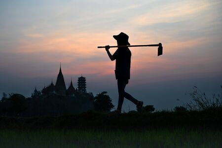 silhouette of farmer walks carry hoe to the rice fiels in the early morning, living life of Thai culture traditional life in Countryside, with temple pagoda in background