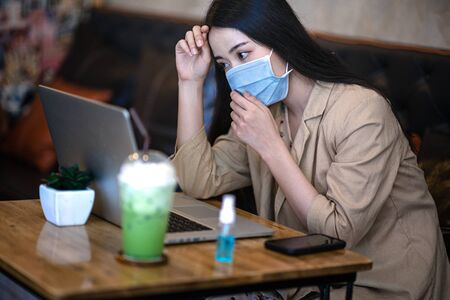 woman wearing protection mask with alcohol always cleaning hand against infection of covid-19, in worry and serious motion of woman working outdoors in situation of virus infect