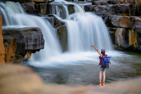 Woman traveller backpacker enjoy motion sightseeing to see jungle waterfalls in rainforest tropical at summertime and long weekend vacation trip, disconnected and away from the place of crowd