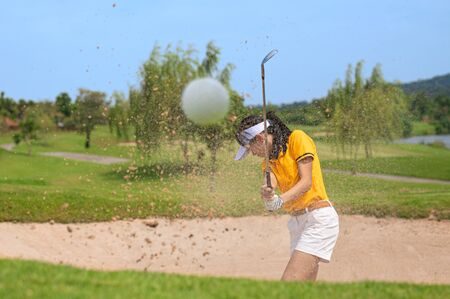 Woman golf player in concentrate action of hitting golf ball away from a trouble sandbank bunker in golf course, trouble away keep going concentrate to final destination