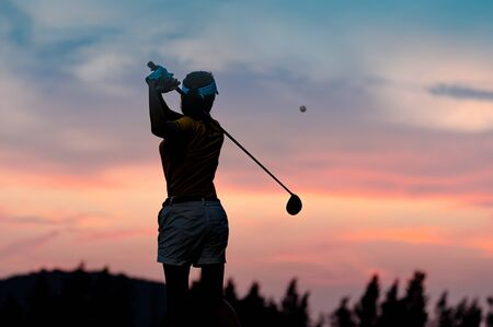 silhouette of woman golf player in action at the end of backswing after hit a golf ball to destination in the fairway, best concentrate to destination of life CONCEPT