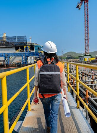 Woman engineering walks step safety under handrail gangway of the work job site, at job starting in daily morning works