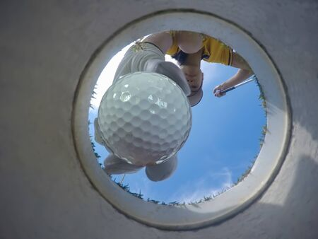 view of bottom low angle of the golf hole, a golf ball in hand of golf player being takes away from the hole on the green by woman golf player after putted successfully a winner