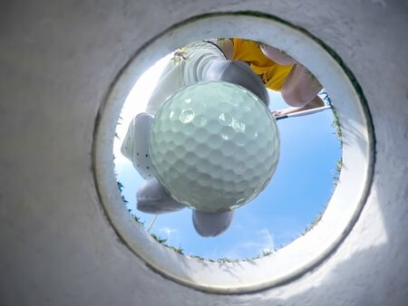 view of bottom low angle of the golf hole, a golf ball in hand of golf player being takes away from the hole on the green by woman golf player after putted successfully a winner Banque d'images