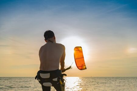 Sport man enjoy playing in the sea kite surf at sunset in summertime vacation, sea sport, aim to destination of life