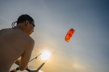 Sport man enjoy playing in the sea kite surf at sunset in summertime vacation, sea sport