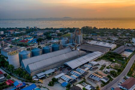 feed mill factory in production line at sunset and sea view in back ground, factory produce line of industrial estate area locate in middle of the city town against air pollution Фото со стока