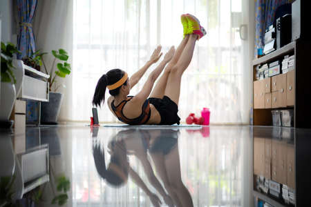 Woman workout exercise at home under situation of virus infection COVID 16, workout from home at time of COVID 19 with social distancing