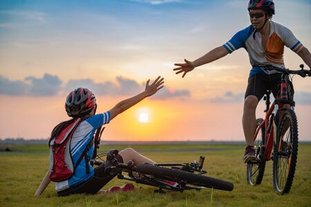 Accident of bicycle clash and failure rise up of woman need hand help hold of man to support, help and assist of the life together in family at worth situation CONCEPT