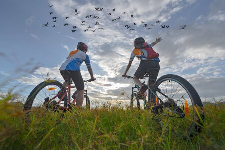 family couple lover enjoy the life of biking on the fresh field meadow grass, cheerfully life together outdoors