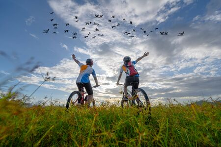 family couple lover enjoy the life of riding biking on the fresh field meadow grass, cheerfully life rise hand up together on outdoors activity