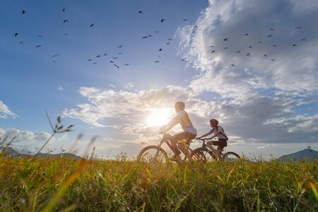 family couple lover enjoy the life of riding biking on the fresh field meadow grass, cheerfully life holding hand together on outdoors activity Stok Fotoğraf