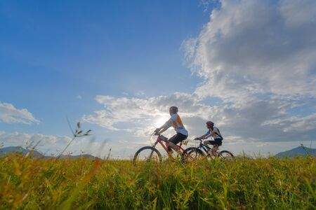 family couple lover enjoy the life of riding biking on the fresh field meadow grass, cheerfully life holding hand together on outdoors activity Фото со стока