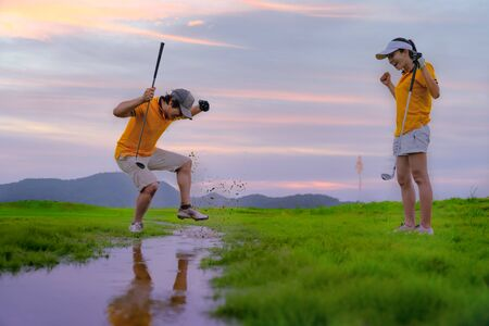 an upset and angry of a man golf player steps drub or stamp on the water splash after found a golf ball hit dropped in the water hazard difficult area, golf-mate or competitor cheerfully mock up in background