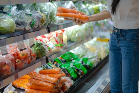 hand of woman wifehouse holds and takes fresh vegetables in shelf cabinet in supermarket