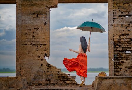woman fashion dress standing on the retro old cottage house in the lake, holding umbrella under raining season Фото со стока