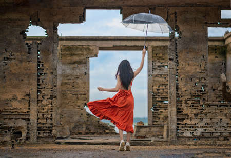 woman fashion dress cheerfully jump on the retro old cottage house in the lake, holding umbrella under raining season Фото со стока