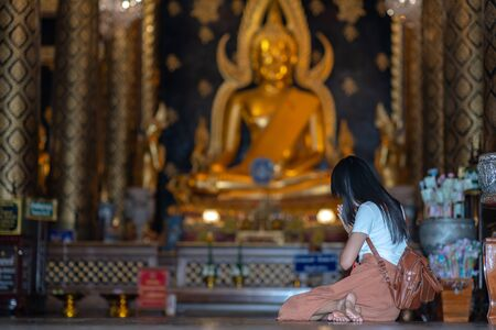 Woman traveller pray respect to the buddha statue in the temple, Thai and Asia traditional and culture in religion spiritual