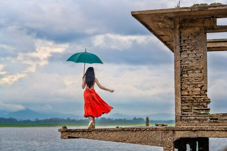 woman fashion dress walking on the retro old cottage house in the lake, holding umbrella under raining season