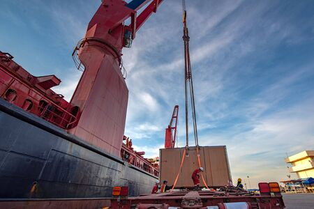 Package unit of the heavy life cargo being discharging or loading by the ship crane under supervisor by professional handling in the port terminal
