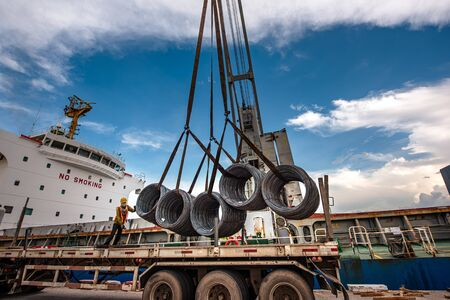Cargo shipment of steel coils being loading or discharging by the workers stevedore man in the port under handle by the ship crane with the lorry trailer transport delivery under hooks, working in port terminal operation the shipment export and import Фото со стока