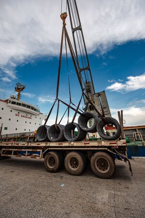 Cargo shipment of steel coil being loading or discharging by the workers stevedore man in the port under handle by the ship crane with the lorry trailer transport delivery under hooks in port terminal