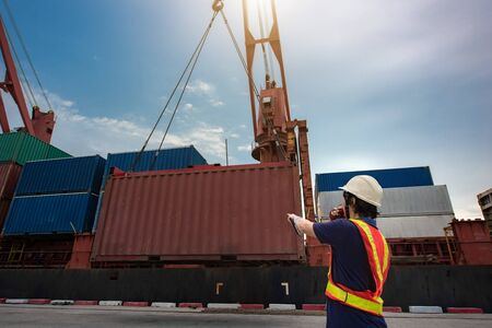 Loading master, port control or stevedore takes control working at job site in port terminal, loading operation in port terminal under regulation safe working place Фото со стока