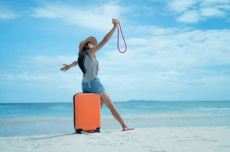 Woman tourist traveller standing on the sea beach ready going to the trip journey to explore the World