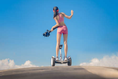 woman sporty riding scooter upon the hill holding gimbal camera to takes VDO capture moving object