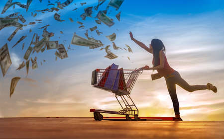 Shopping woman in action of chasing money spending with  shopping cart pushing, consumption a lot of money of shopping woman concept