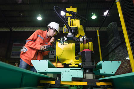 woman working engineering or technical inspection the system  of machinery to ensure working in order by checklist part and quality control Stockfoto