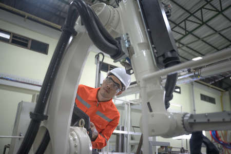 supervisor inspect or testing the system of robotic brand new in smart factory modern, working robotic machinery working together with human control in modern factory