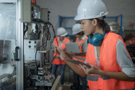 woman working engineering or technical inspection the system  of machinery to ensure working in order by checklist part and quality control, workplace with teamwork together Archivio Fotografico