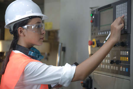 Woman engineering in charge of working duty in dashboard controller of the machine operation in manufactory warehouse