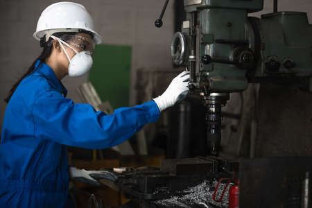Woman engineering technician working on machinery drilling metal with with job in working carefully handle