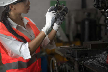 Woman engineering technician or inspection quality control working on machinery drilling metal with measurement focus on precision