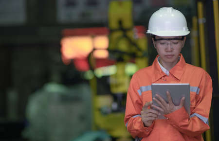 woman working engineering or technical inspection the system  of machinery by online mobile device connecting to ensure working in order by checklist part and quality control