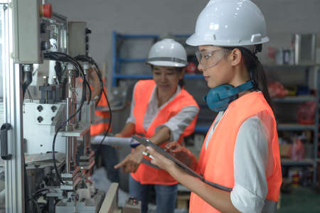 women working engineering or technical inspection the system  of machinery to ensure working in order by checklist part and quality control