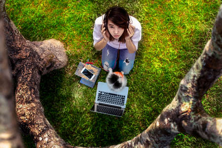 woman girl enjoy reading while listening online music unter curve of the tree with puppy dog playing around on the fine grass field
