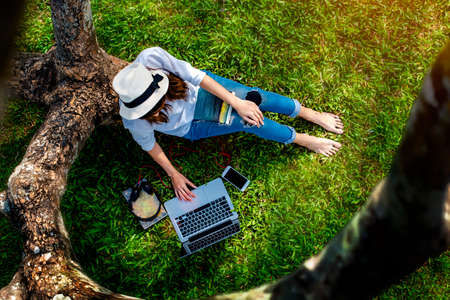 woman girl enjoy reading while listening online music unter curve of the tree with online seaching around on the website, outdoor activity enjoyment