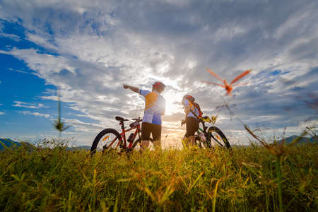 couple lover enjoy riding mountain bicyble adventure touring on the grass meadow at holidays weeken together exercise