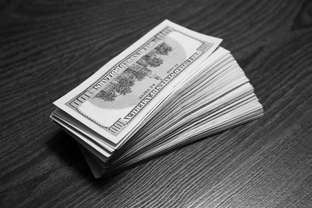 over paying: big pile of money. stack of money. related to money, money on the wooden background