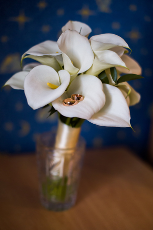 lily flowers: gold wedding rings lie on a bouquet of calla lilies, calla bouquet, rings on a light background